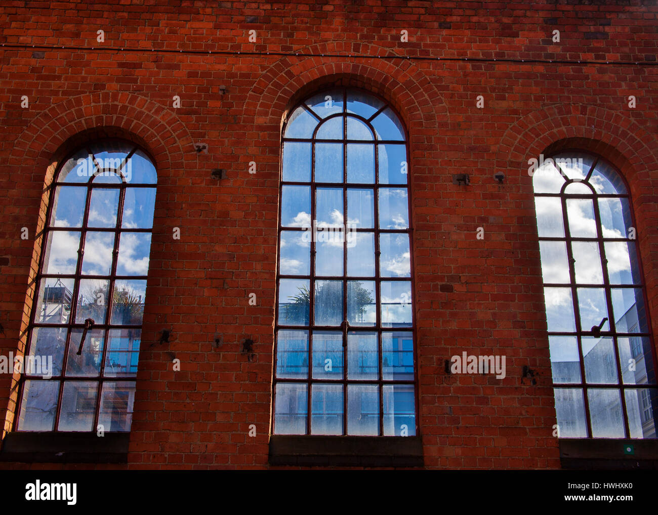 three arched victorian windows showing clouds and sky - Stock Image