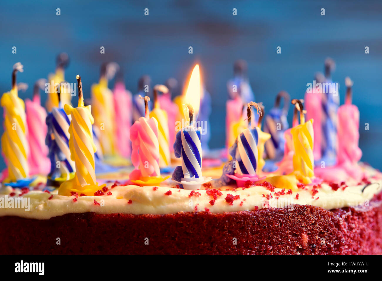 closeup of a cake with some unlit candles and just one lit candle after blowing out the cake - Stock Image
