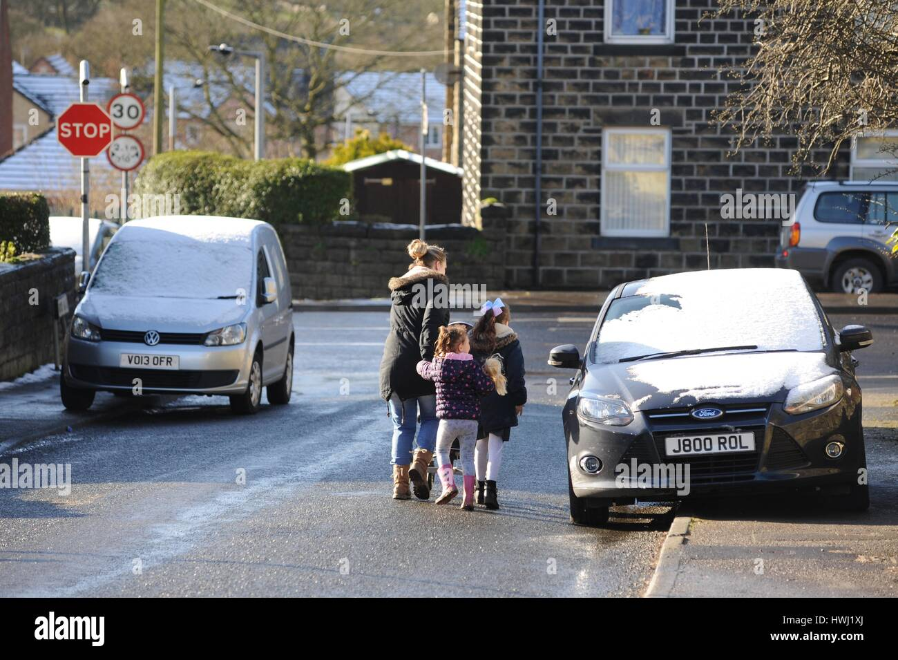 A woman dangerously walks her children around a car which is parked on the pavement. - Stock Image