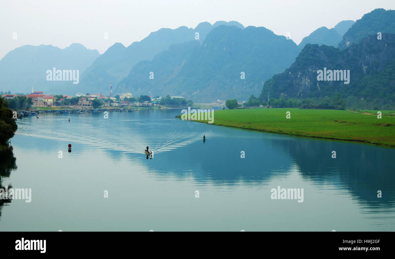 Quang Binh landscape, Viet Nam, boat on river,  riverside house with mountains behind, green field beside, beautiful - Stock Image