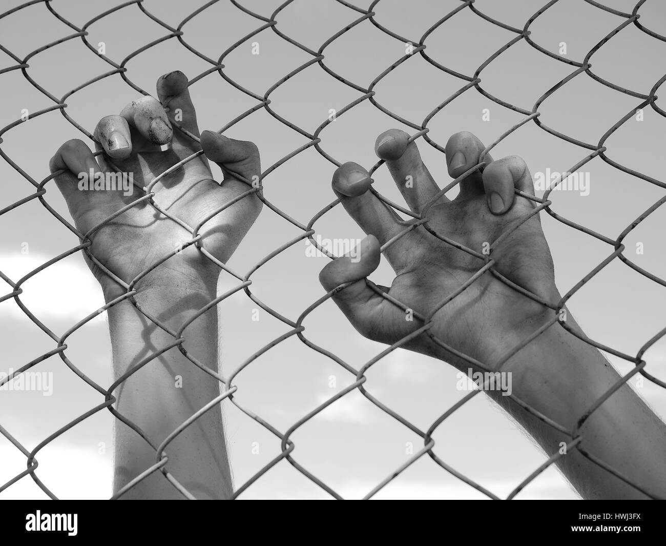 Dirty and discolored hand clinging to a steel wire fence, black and white - Stock Image