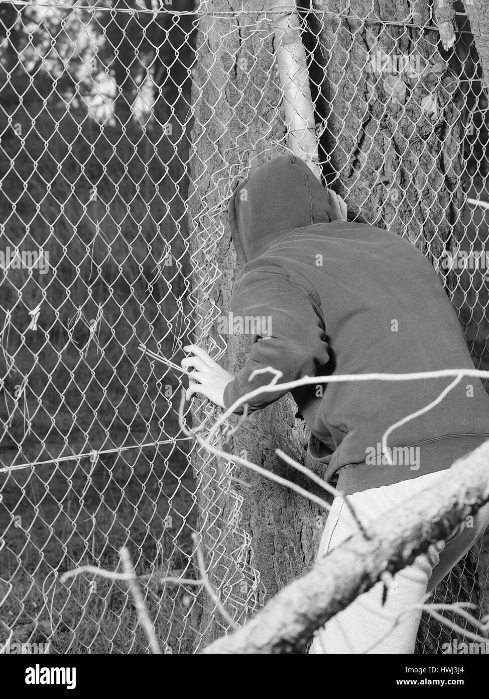 Person crawling through a fence opening with hand clinging to a steel wire , black and white, Australia 2016 - Stock Image