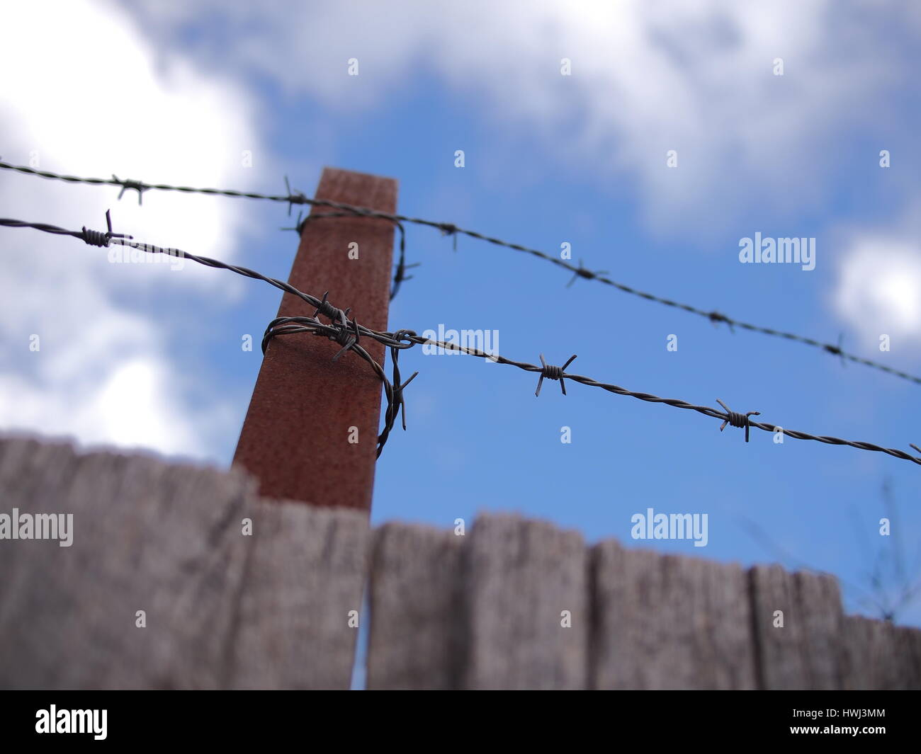 Steel barb wire on a fence under cloudy sky, Australia 2016 - Stock Image