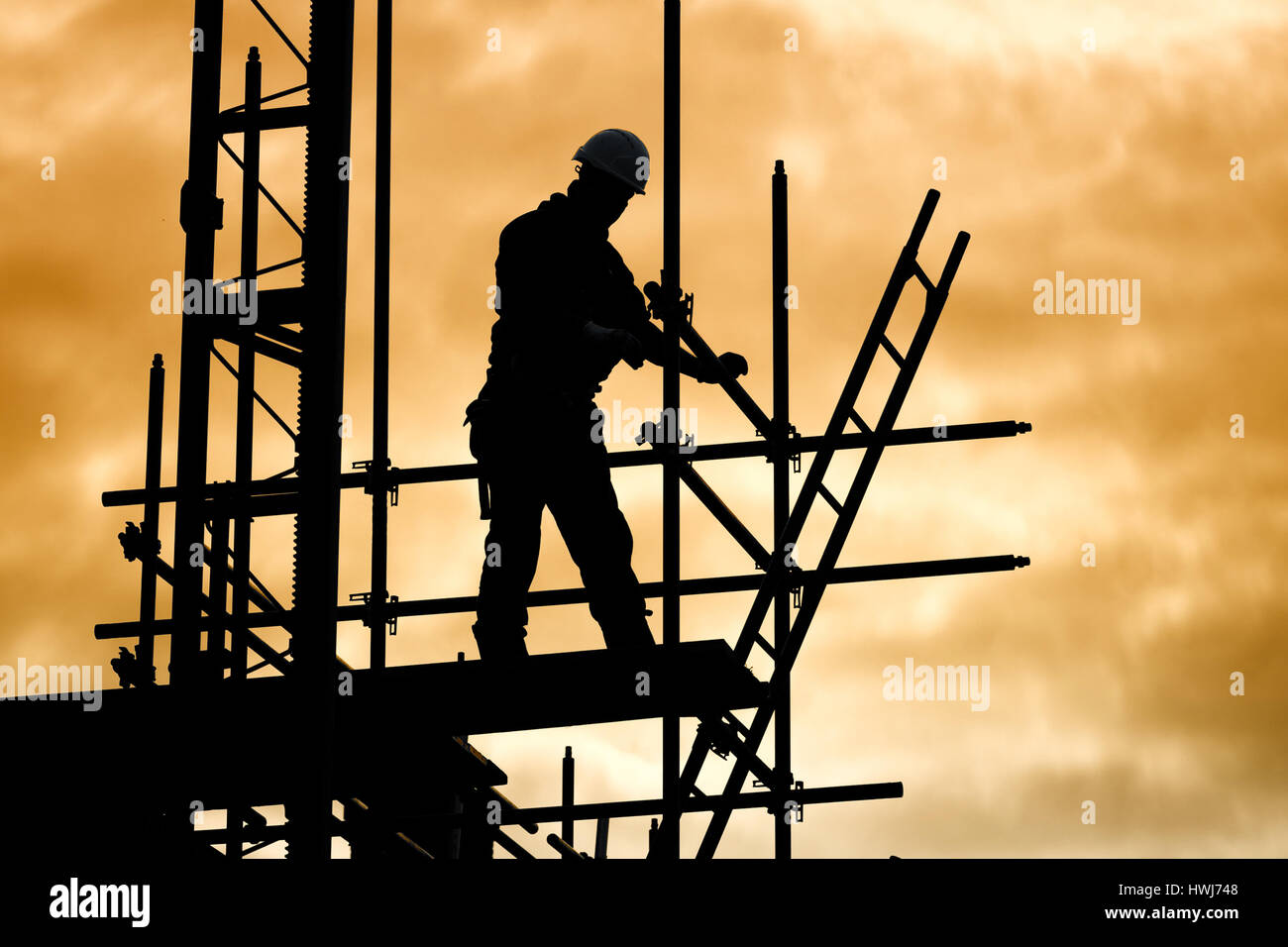 silhouette of construction worker against sky on scaffolding with ladder on building site at sunset - Stock Image