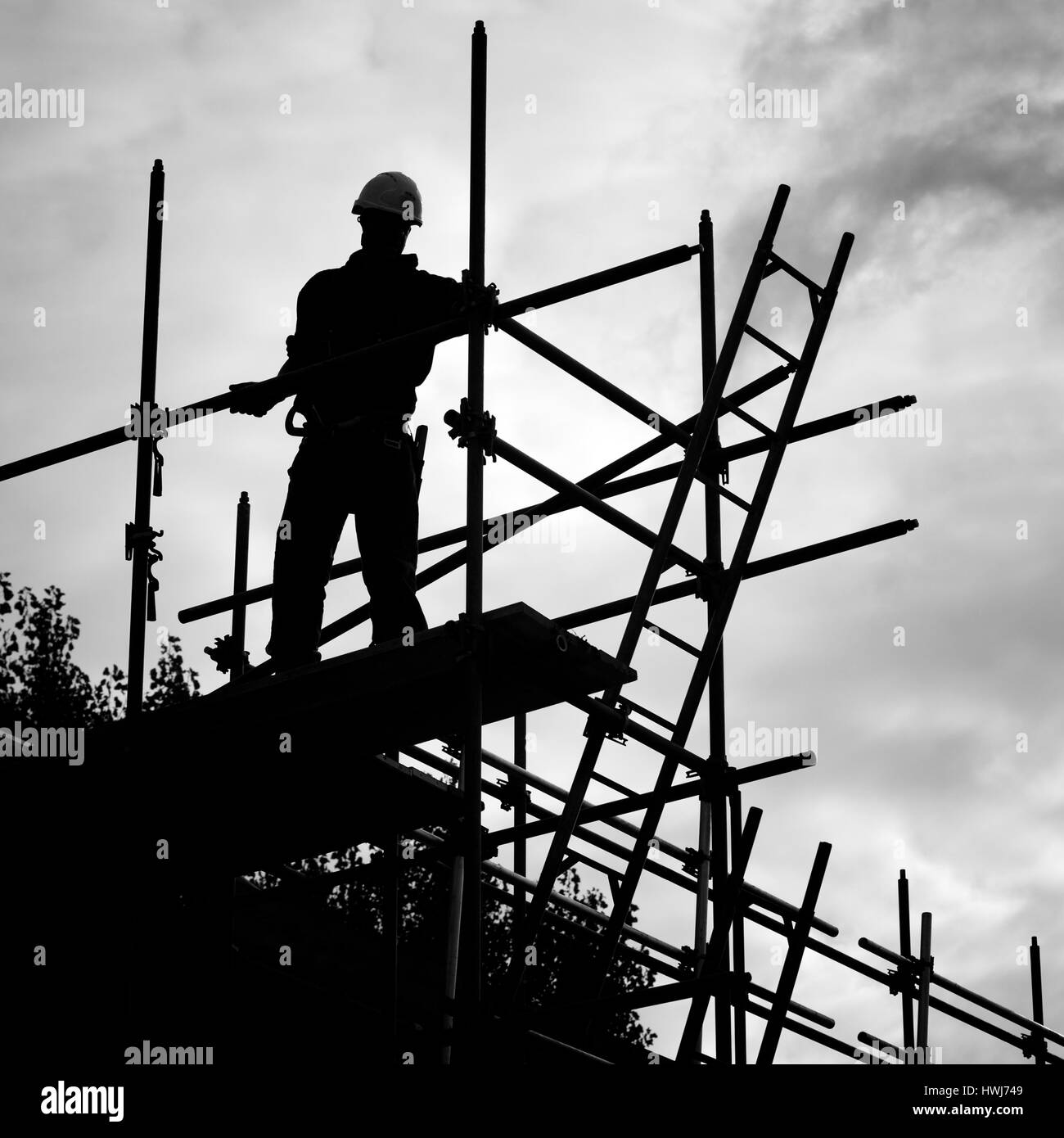 silhouette of construction worker against sky on scaffolding with ladder on building site.Monochrome - Stock Image