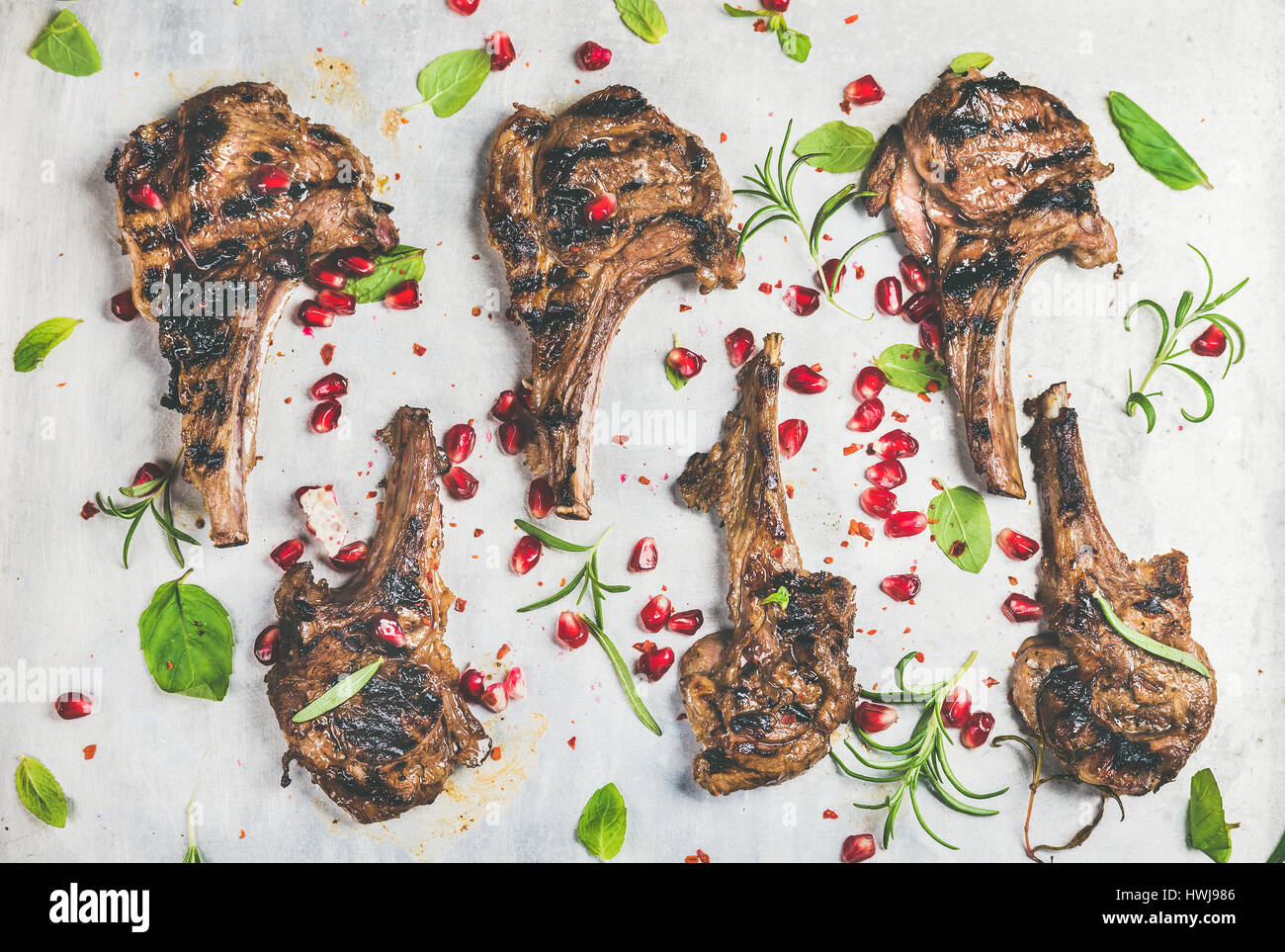 Grilled lamb ribs with pomegranate seeds, fresh mint and rosemary over metal baking tray background, top view, horizontal Stock Photo