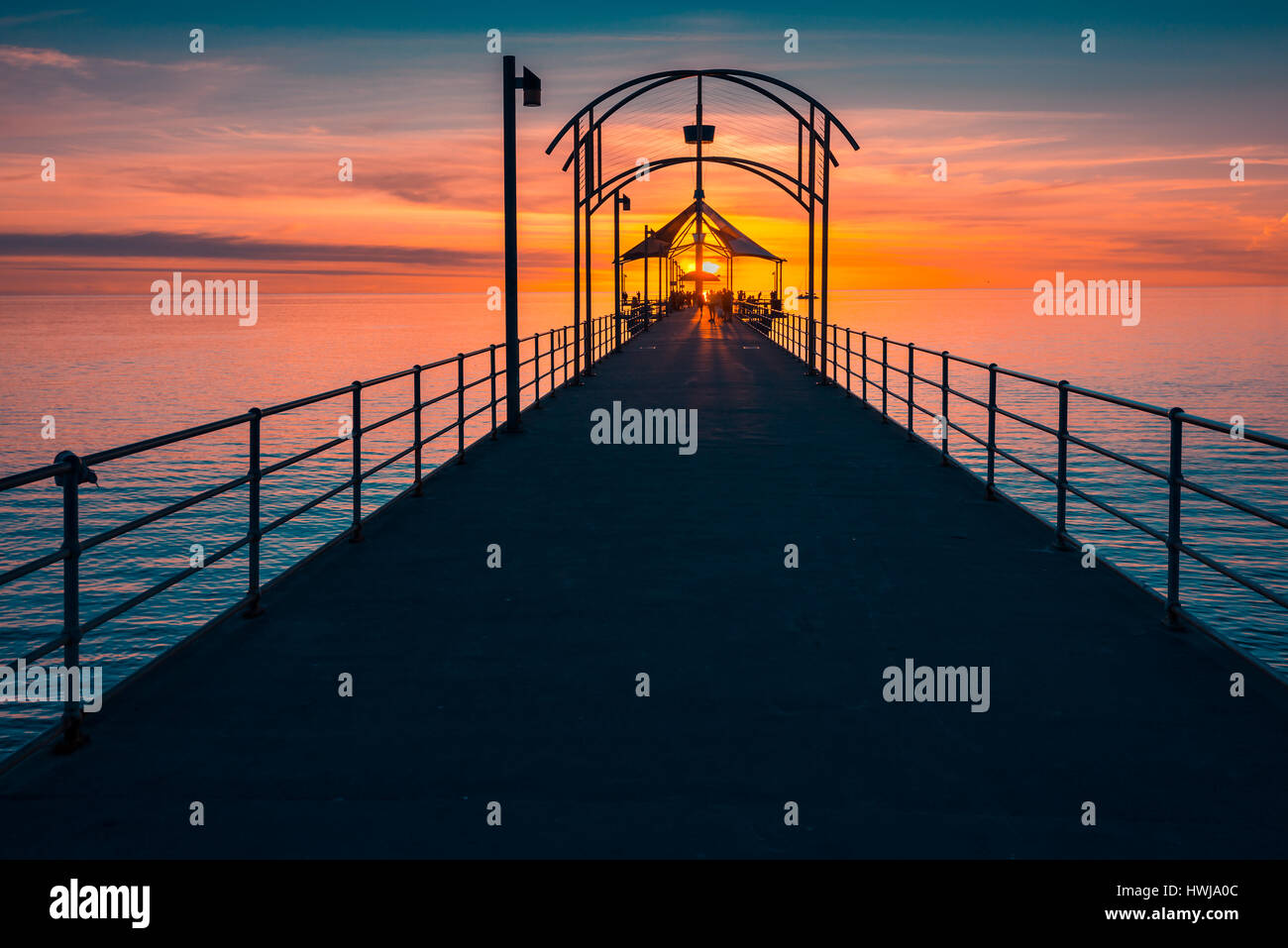 People walking along Brighton Jetty at sunset - Stock Image