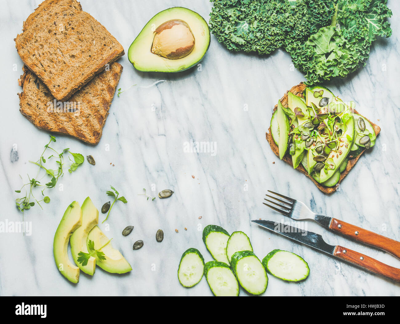Healthy green veggie breakfast concept. Sandwich with avocado, cucumber, kale, kress sprouts, pumpkin seeds over - Stock Image