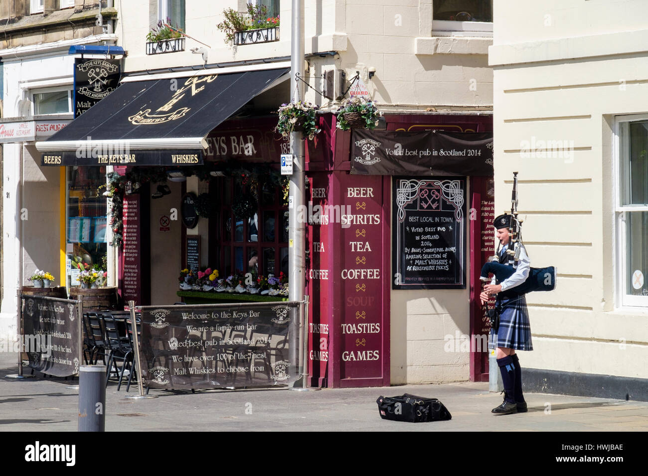 Piper in traditional costume playing bagpipes outside The Keys Bar Inn in town centre. Market Street, Royal Burgh - Stock Image