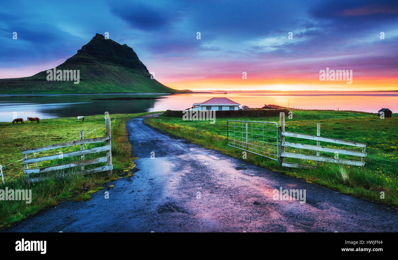 The picturesque sunset over landscapes and waterfalls. Kirkjufell mountain. Iceland - Stock Image