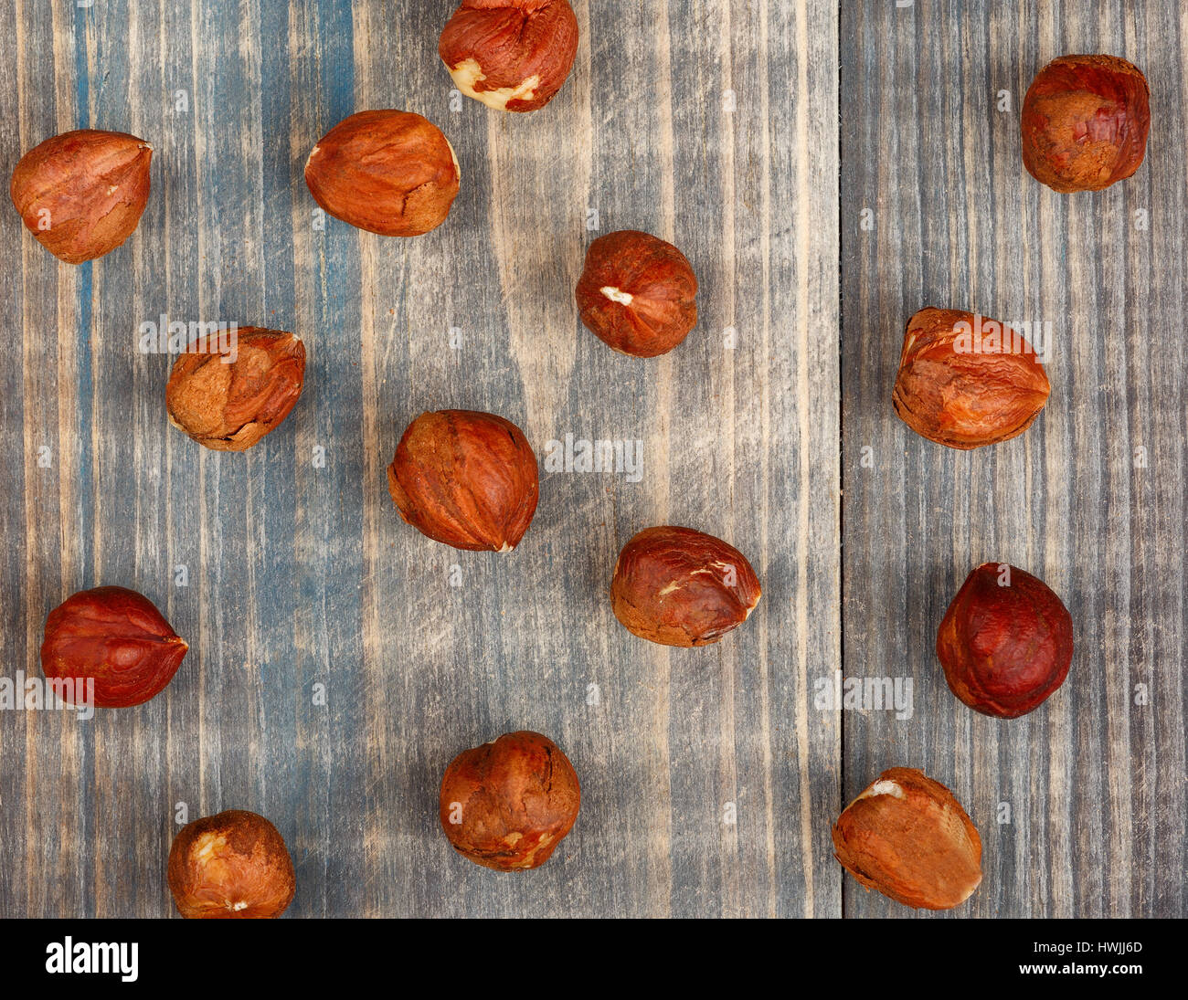 Nuts of hazelnut are scattered on a wooden table Stock Photo
