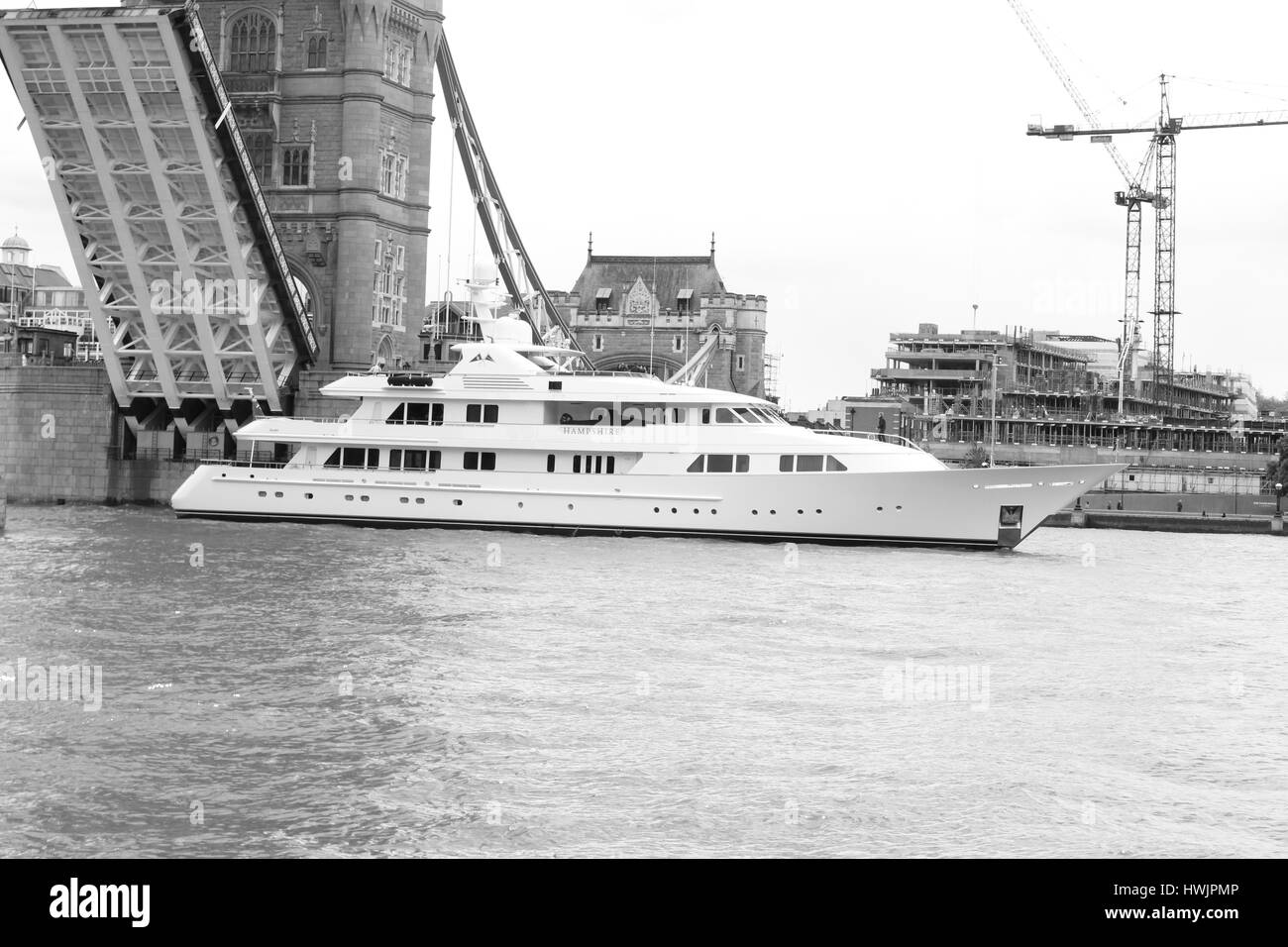boat floating down river thames under tower bridge photographed in black and white Stock Photo