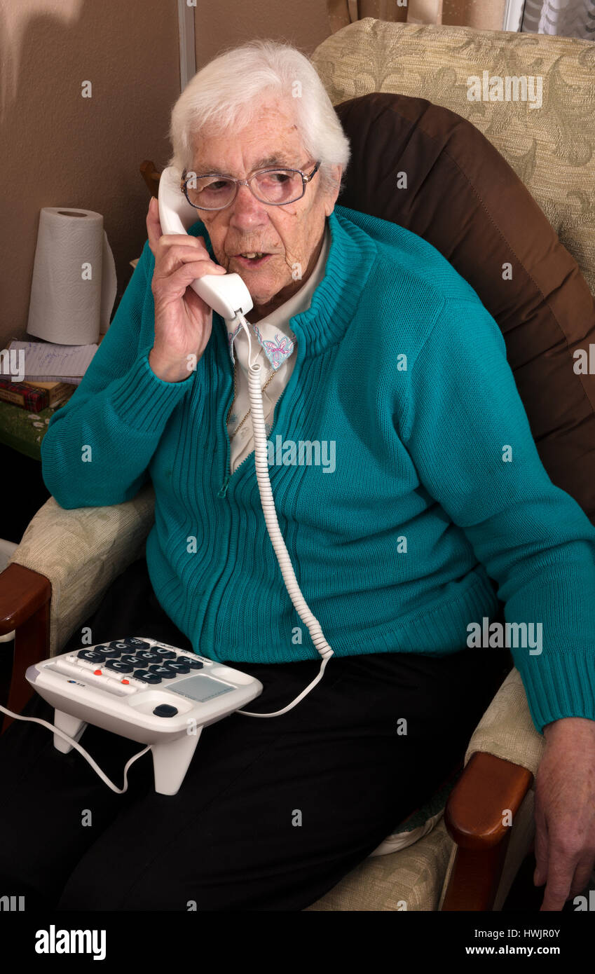 Elderly woman with impaired vision living talking to a friend using a BT large buttoned telephone and landline - Stock Image