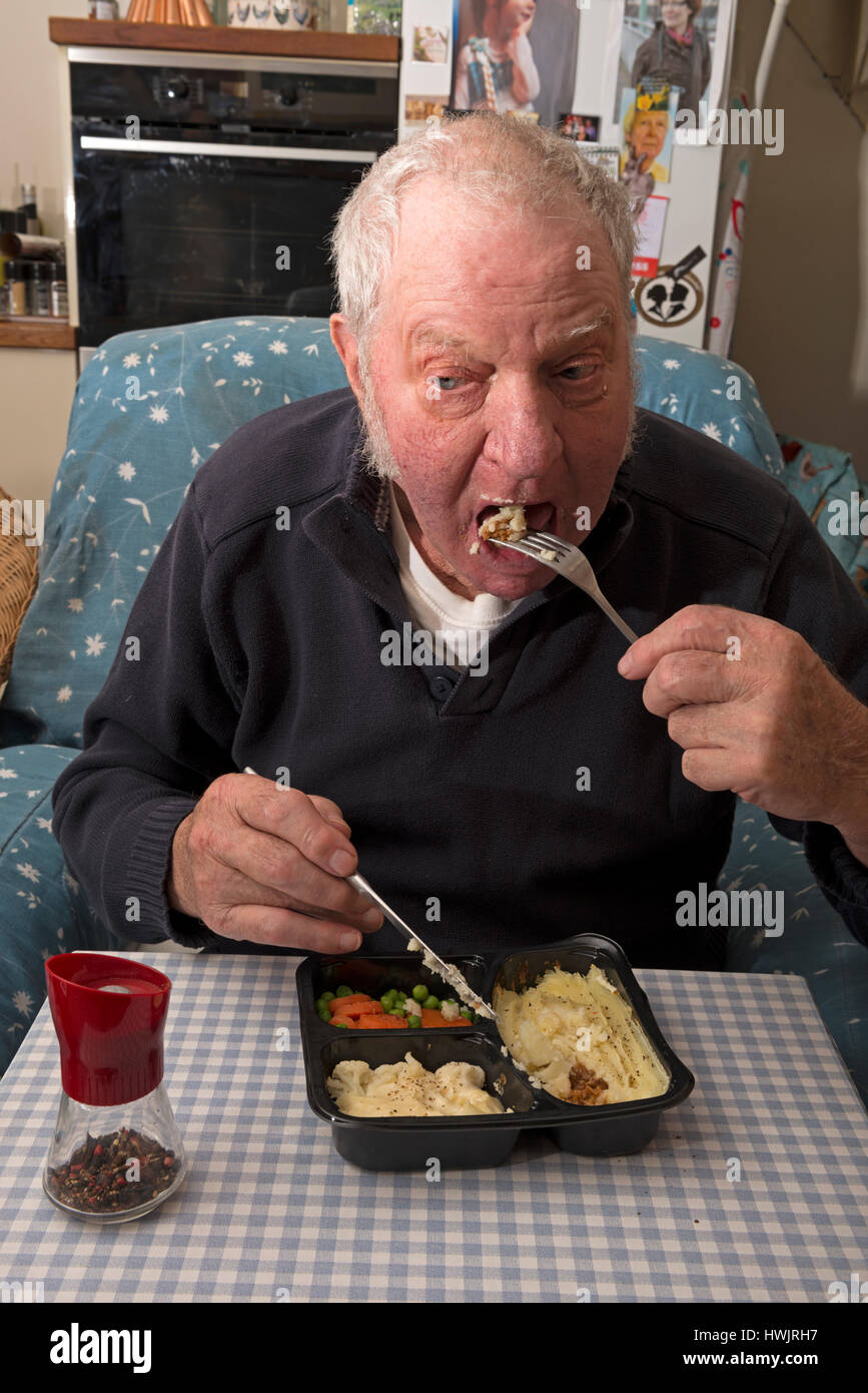 Elderly man eating a cottage pie ready meal - Stock Image