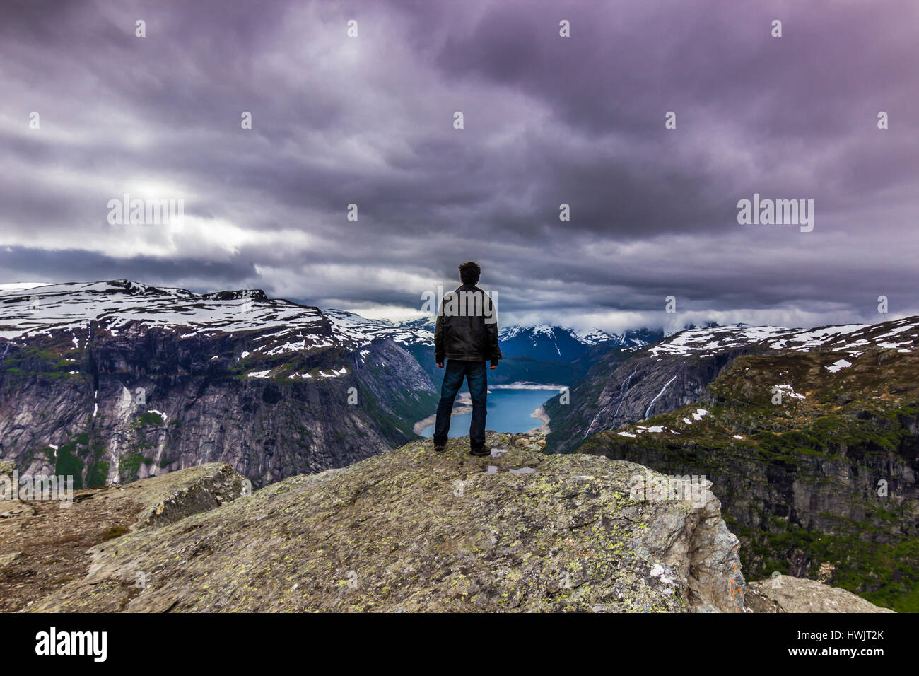 July 22, 2015: Panorama of traveller at the edge of Trolltunga, Norway Stock Photo