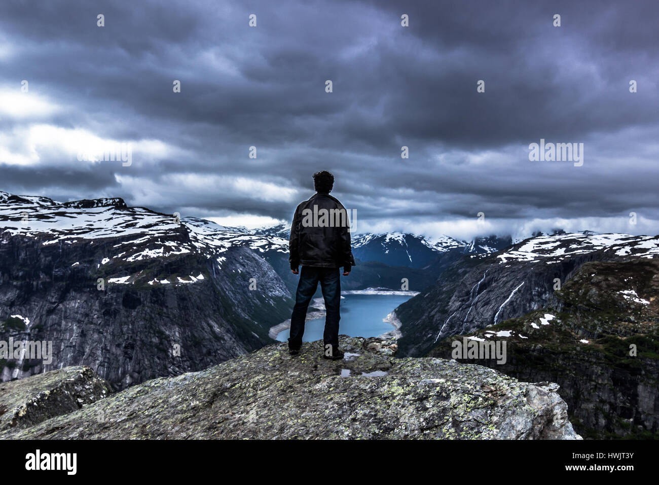 July 22, 2015: Traveller at the edge of Trolltunga, Norway - Stock Image