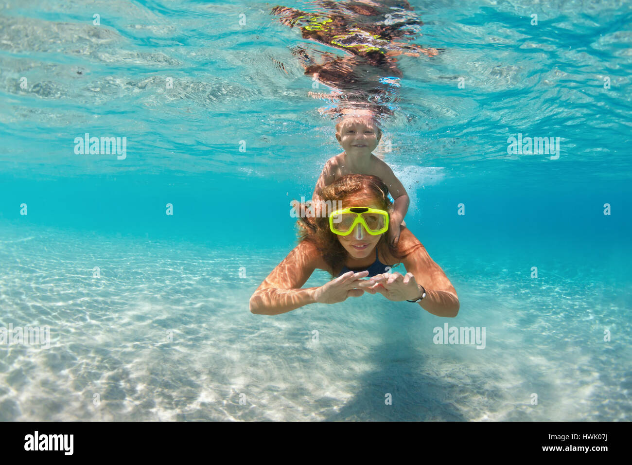 Happy active family - mother, baby son snorkel and dive underwater in sea pool. People lifestyle, water sport outdoor - Stock Image