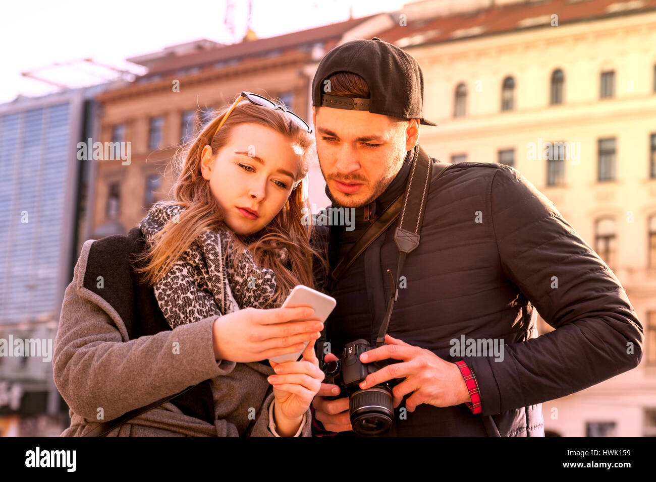 tourists couple tries to find the way on smart phone navigation app - Stock Image