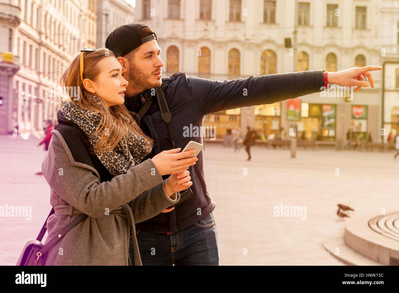 couple tourists in prague lost their orientation in the streets and need to use the gadget with navigation app to - Stock Image