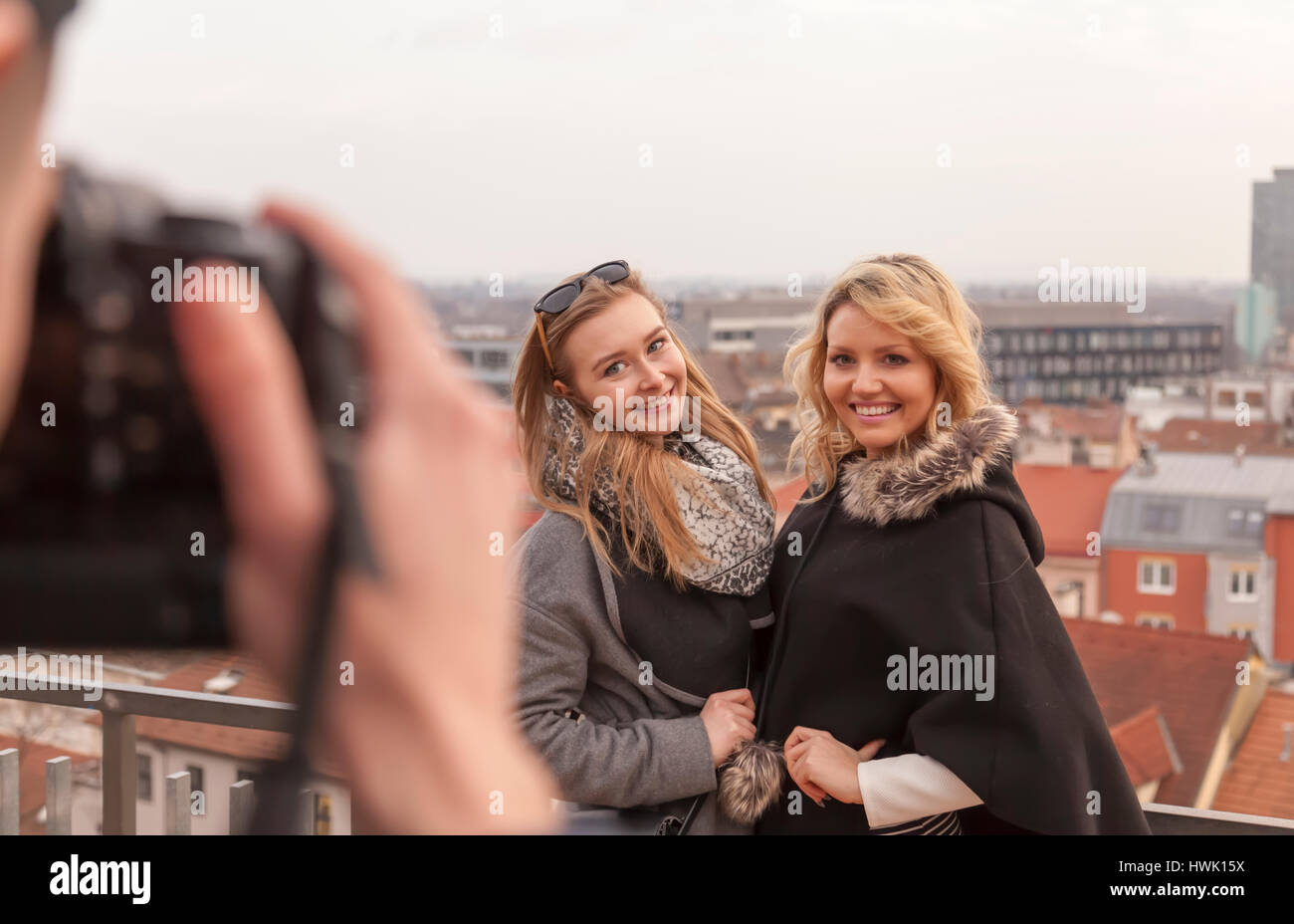 photographer takes pictures of two women in front of city scape. both models are smiling at man taking pictures - Stock Image