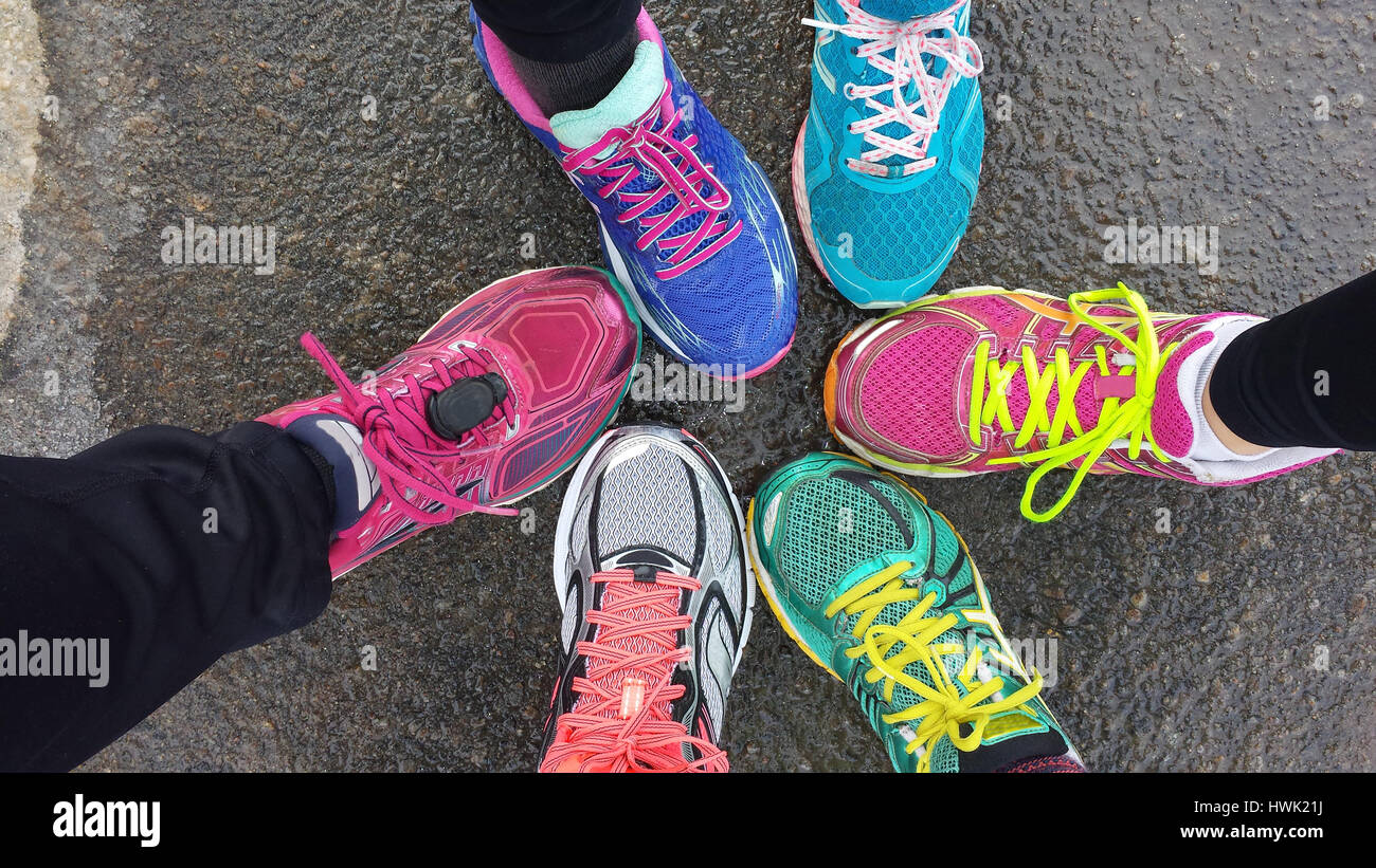 Overhead view of colorful running shoes on runners' feet. Wet pavement, one runner wearing a foot pod for a - Stock Image