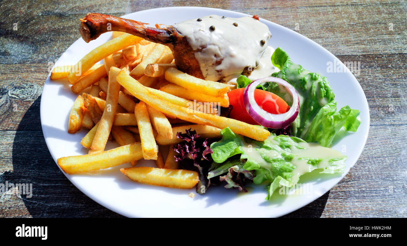 Gourmet food of crispy duck leg confit covered with pepper sauce, with potato fries and lettuce, tomato, onion, - Stock Image