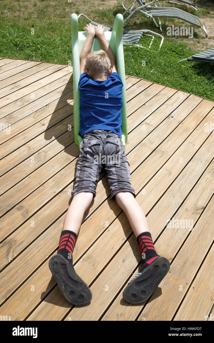 Boy deep in thought laying on a kiddy slide on his deck. Polish child age 12 musing. Zawady Central Poland Europe - Stock Image