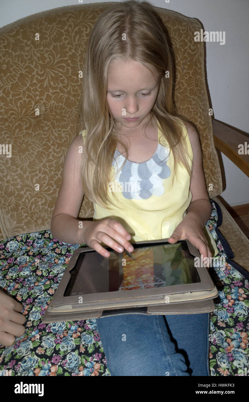 Young girl playing a video game on her ipad or tablet. Polish girl age 8 working her electronic device. Zawady Central - Stock Image