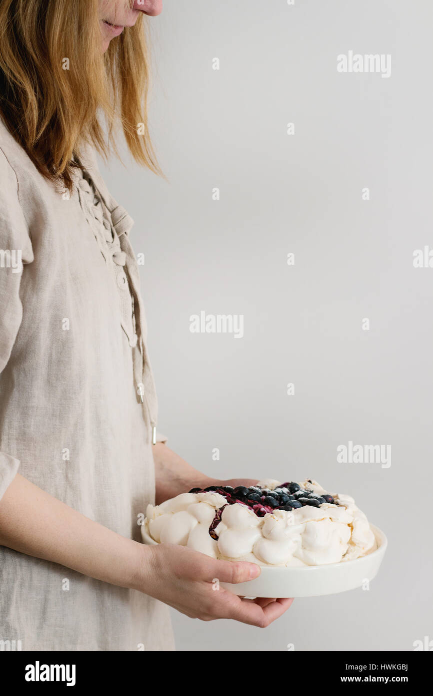 Meringue cake Pavlova in female hands - Stock Image