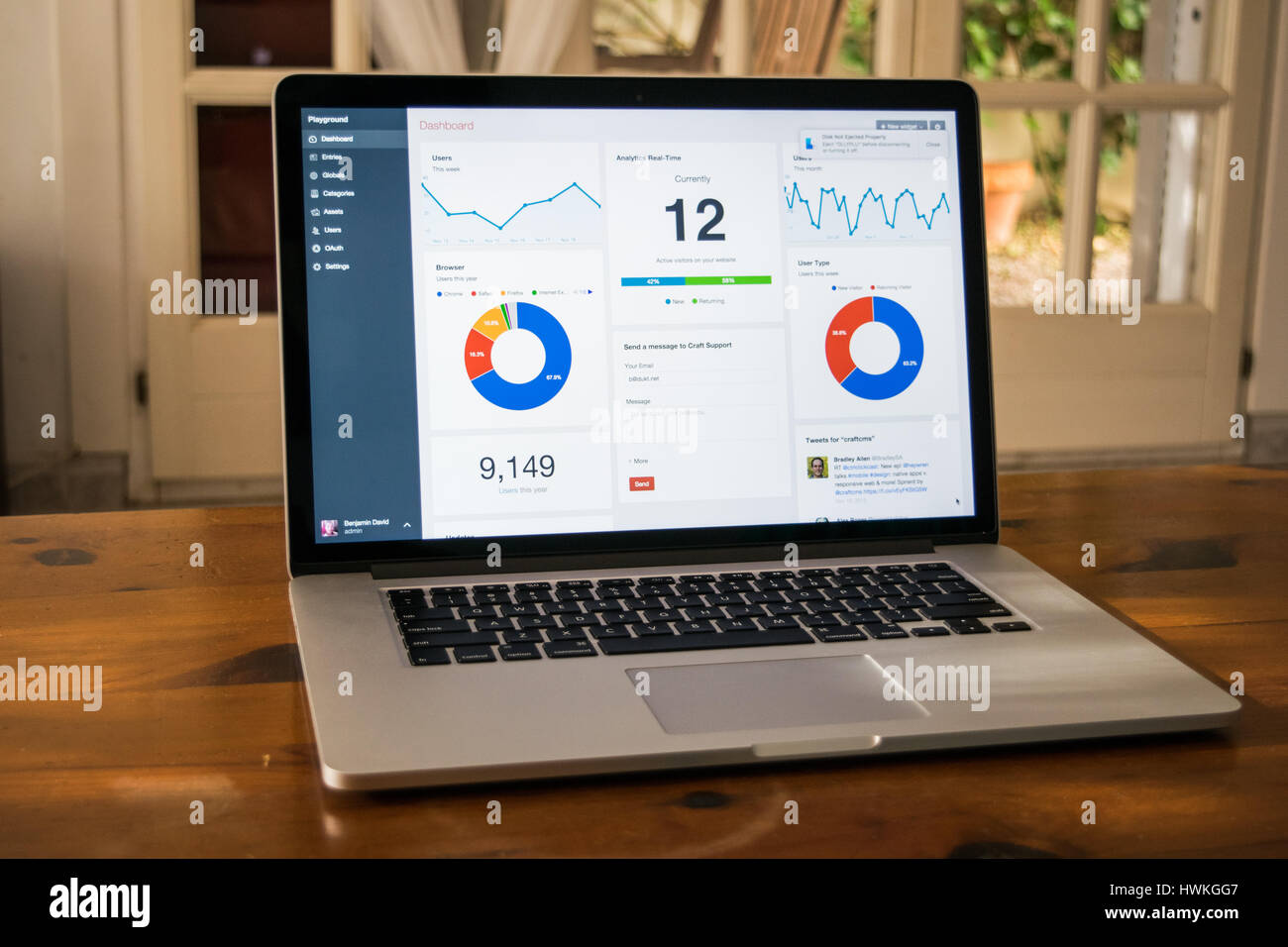 Silver laptop with analytical graph on the screen on the wooden table in home interior - Stock Image