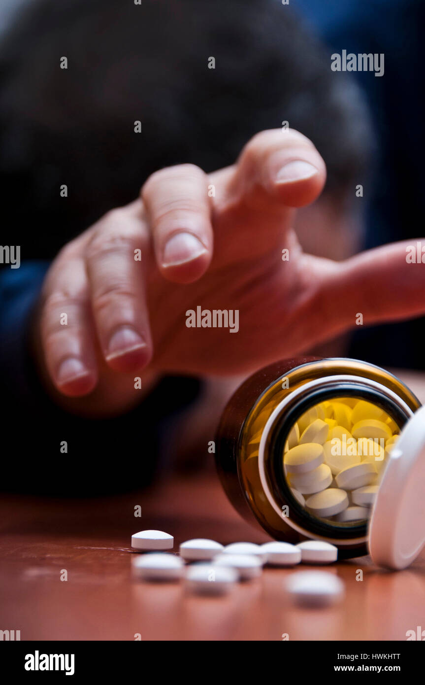 man desperately reaching for drugs - Stock Image