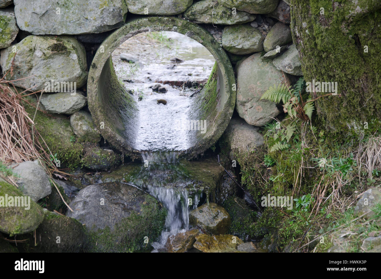 Water pipe drainage in the stone wall around a field Stock Photo