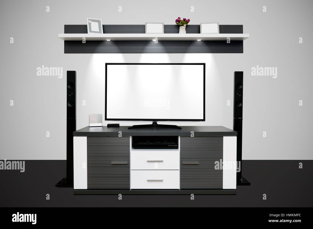 Modern TV room with illuminated LED lamps in shelf - Stock Image