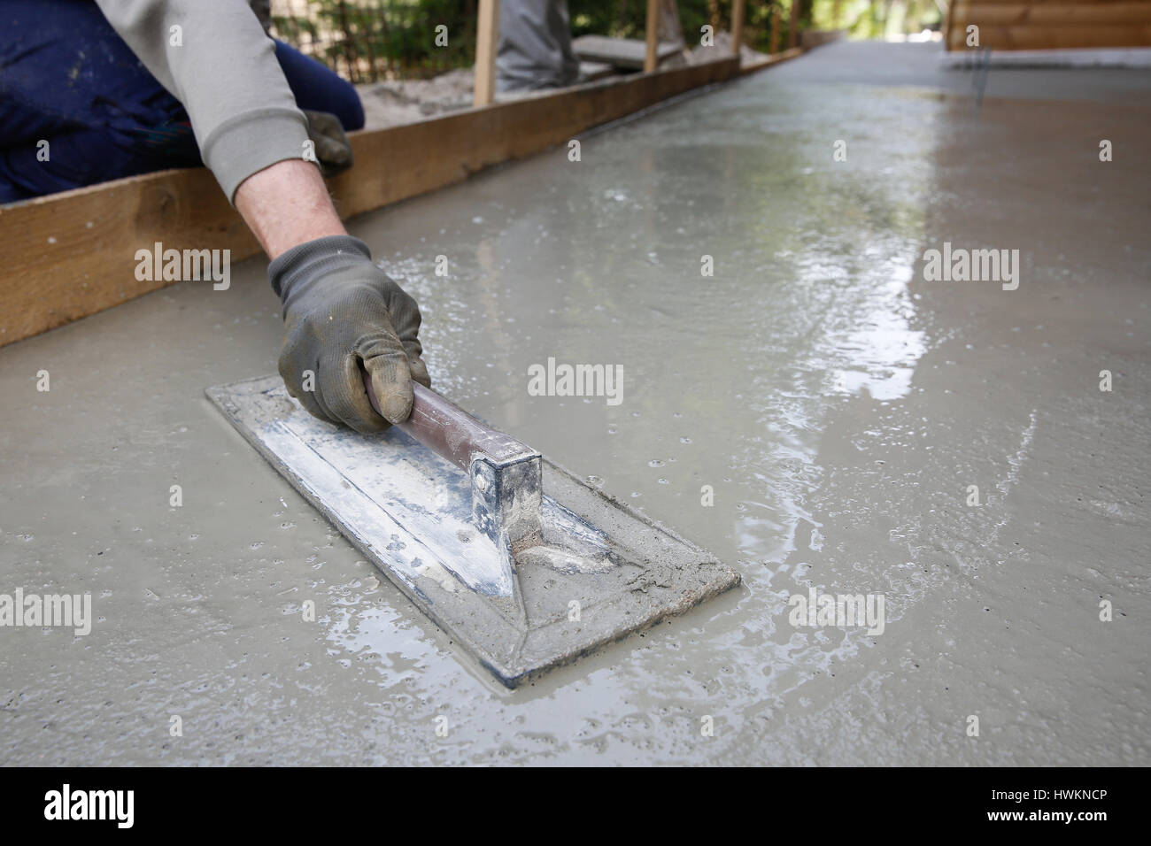Mason leveling and screeding concrete floor base with square trowel mason leveling and screeding concrete floor base with square trowel in front of the house construction business do it yourself precision work aroun solutioingenieria Choice Image