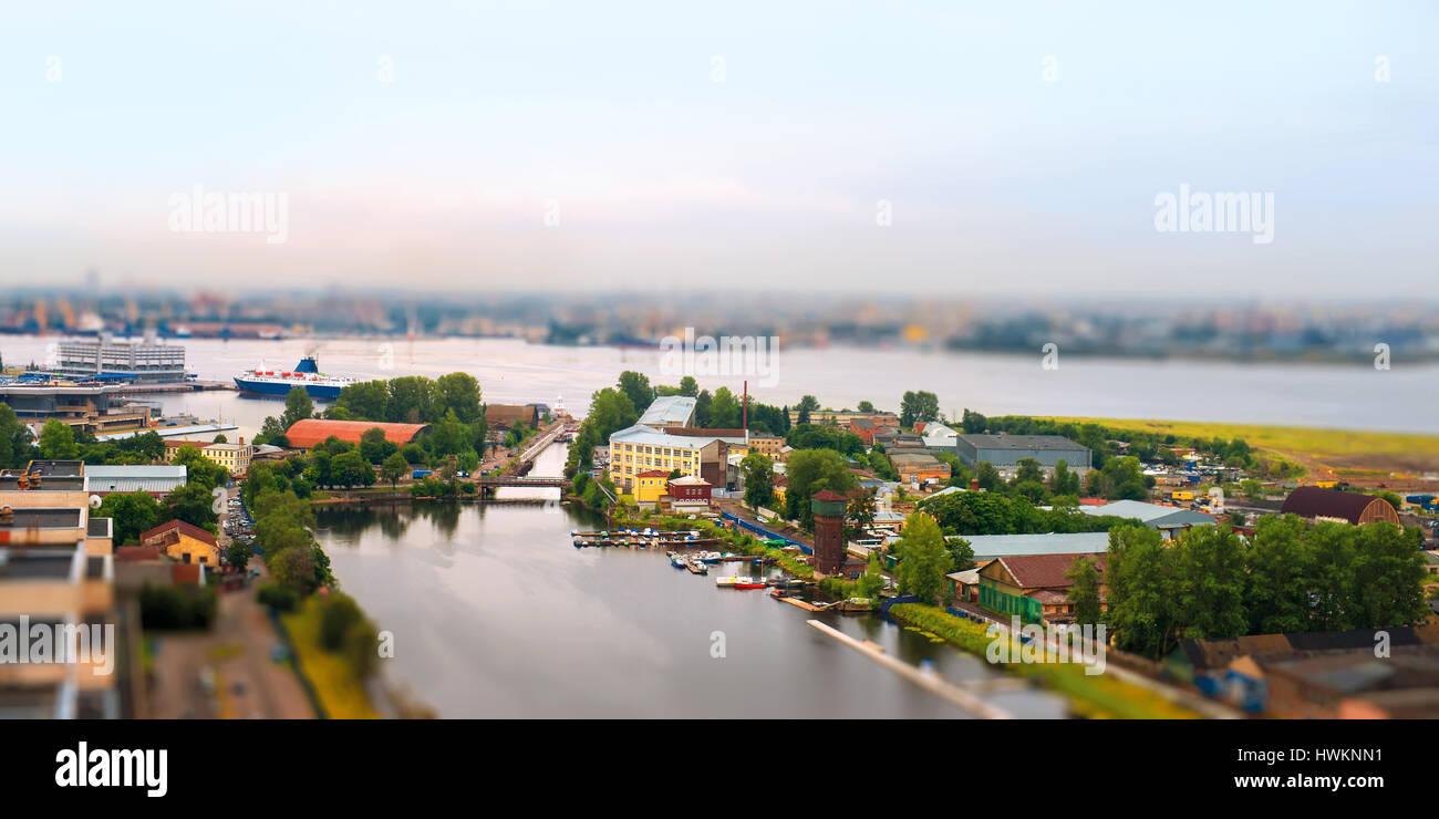 Toy riverside landscape. River, sea, marine station and industrial buildings . Tilt-shift effect, Saint Petersburg, - Stock Image