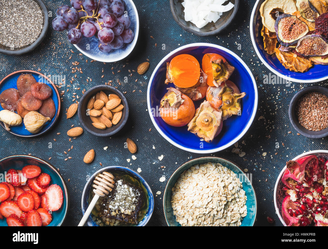 Ingredients in bowls for healthy breakfast over dark blue background, top view. Fresh and dried fruit, chia seeds, - Stock Image