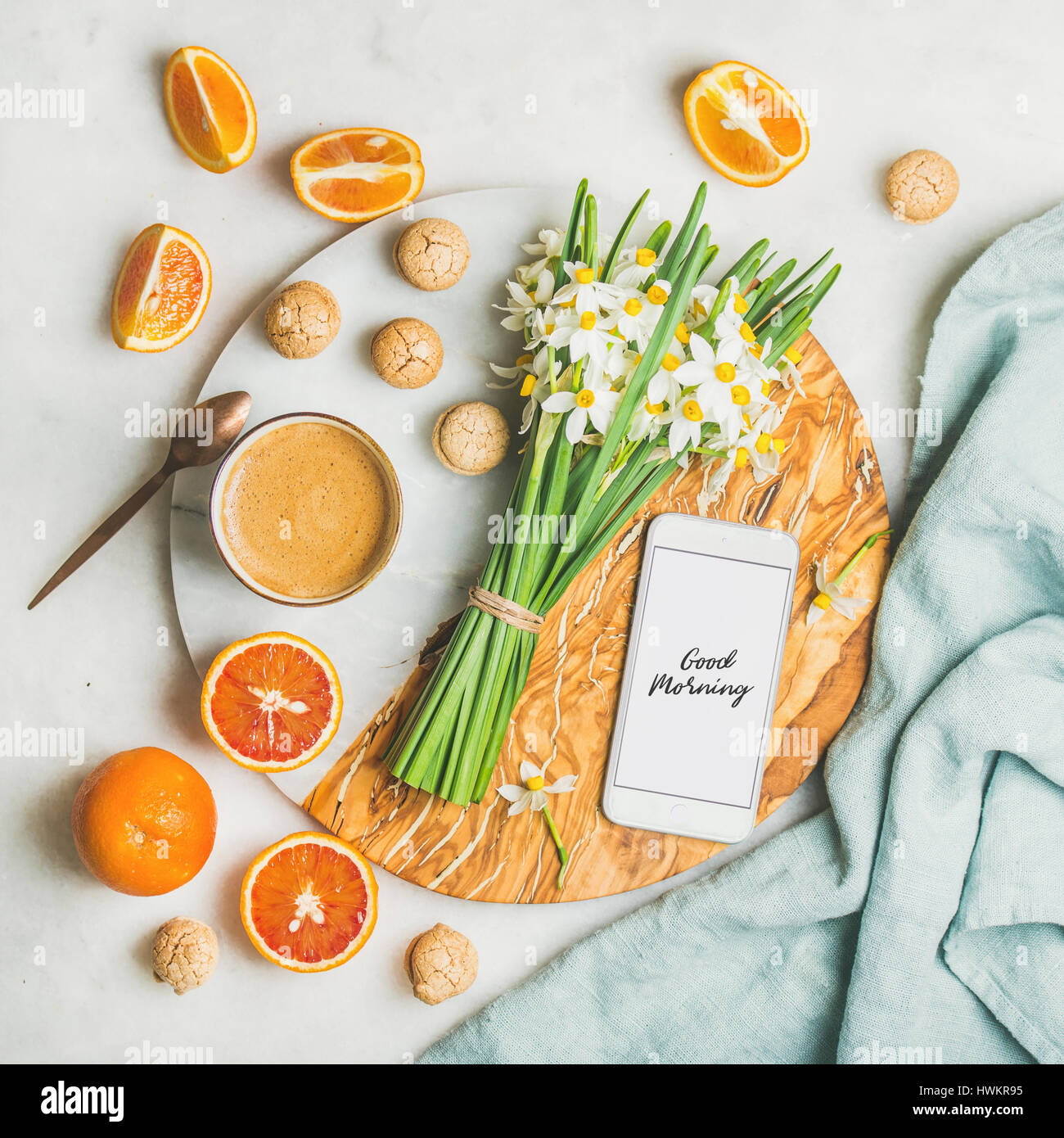 Coffee, cookies, oranges, flowers and mobile phone with Good morning - Stock Image