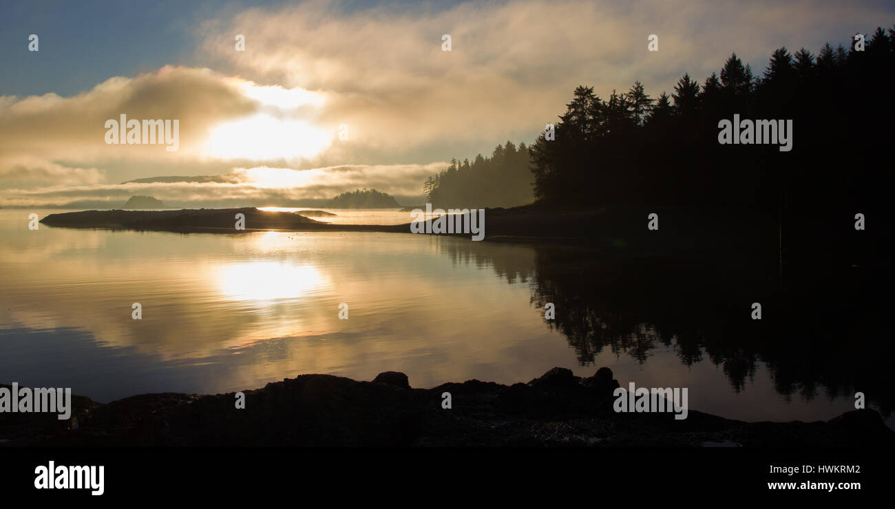 Misty sunrise over low tide exposed rocks on a calm morning at Queen Charlotte City, Haida Qwaii, British Columbia, - Stock Image