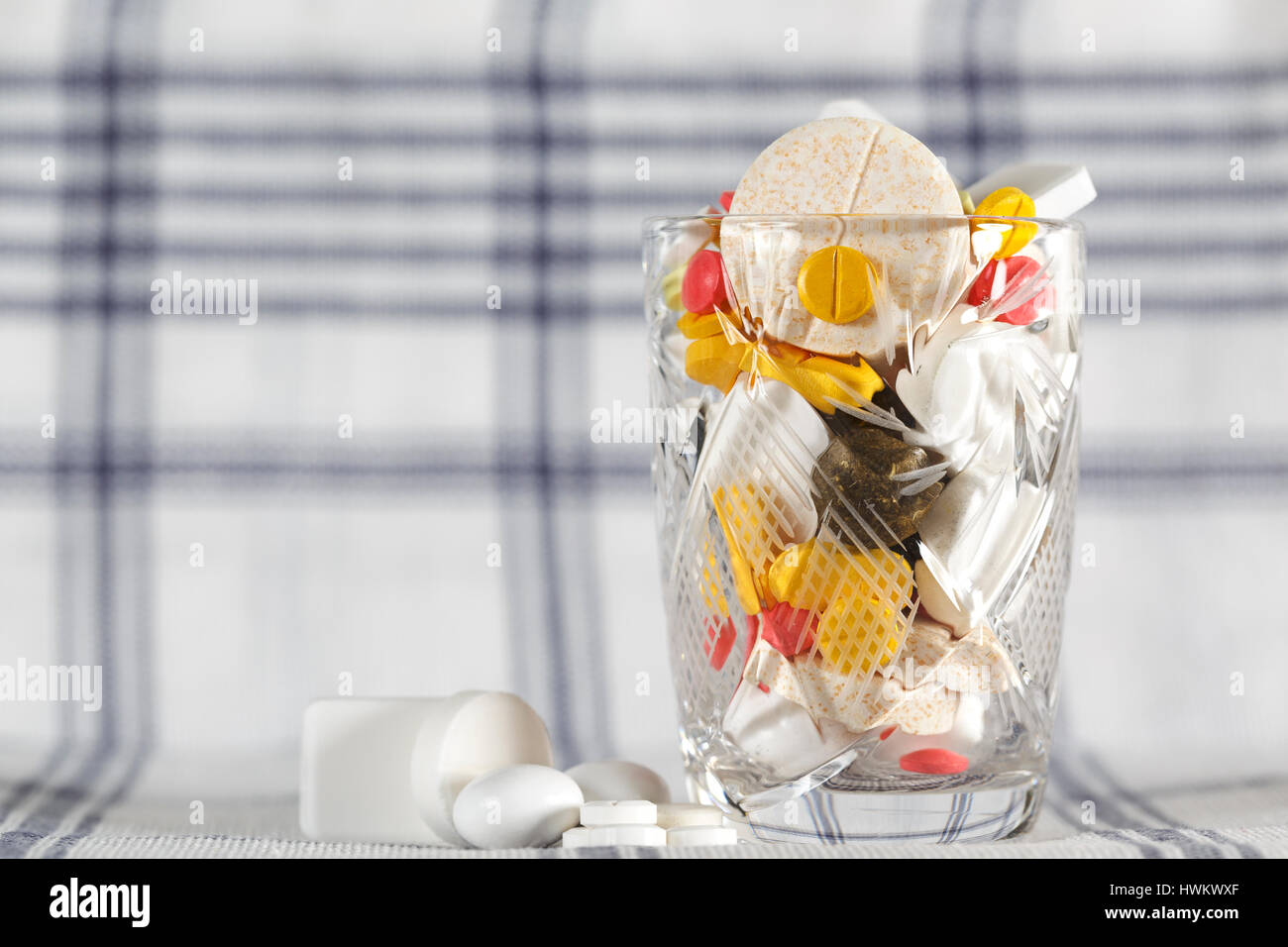 Overdose of medicines is excessive number of pills and this has been shown in a glass filled to the brim - Stock Image