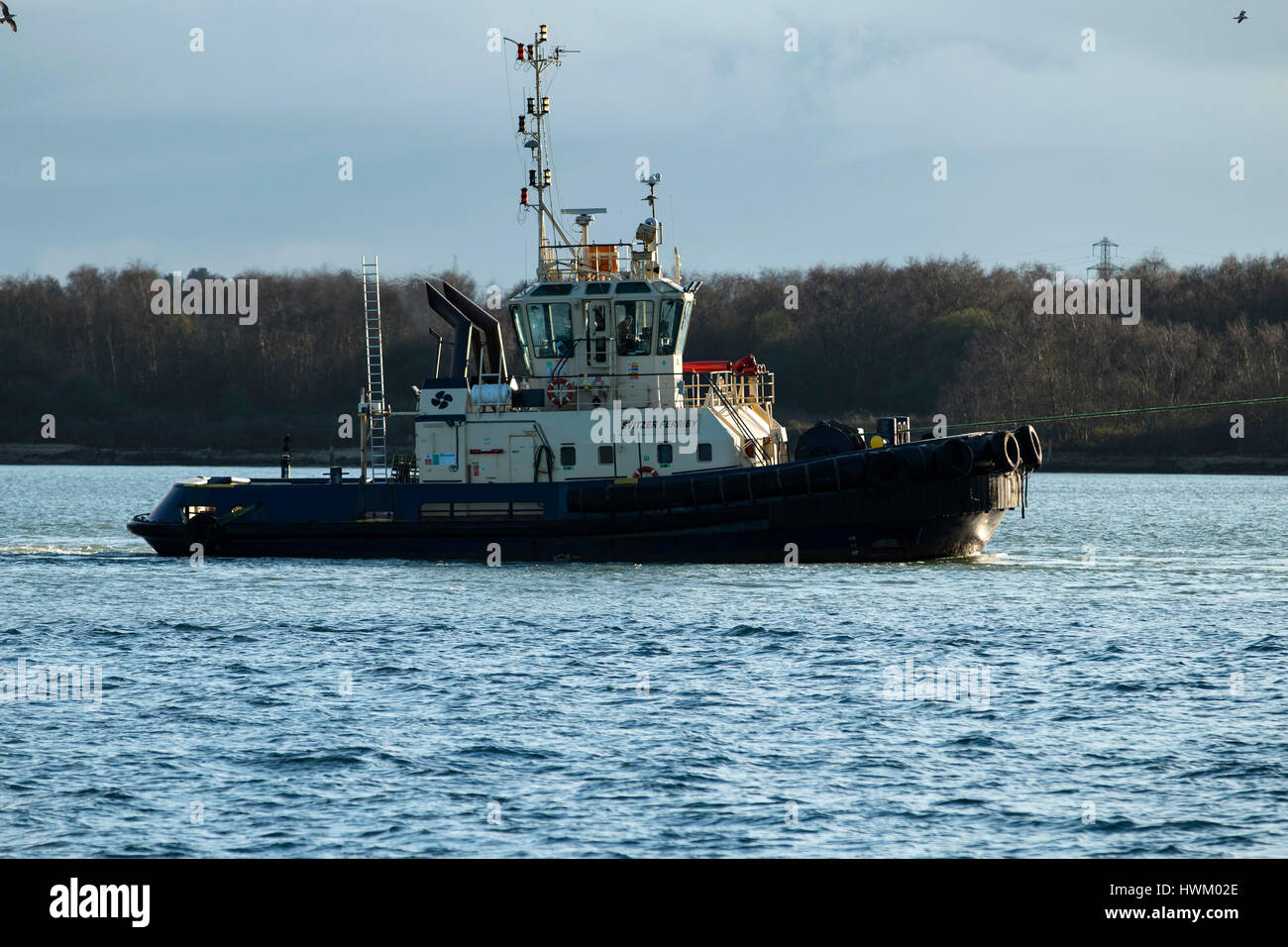 Tug boat Svitzer Ferriby attending the giant container ship CMA CGM Benjamin Franklin at Southampton, UK on 20 March - Stock Image