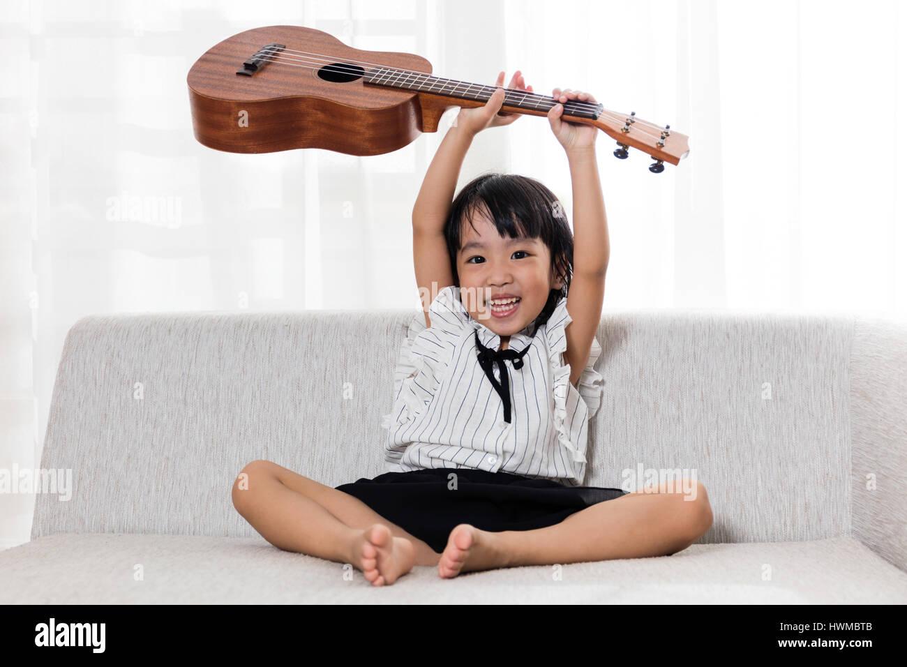 Happy Asian Chinese little girl sitting on the sofa playing ukele Stock Photo
