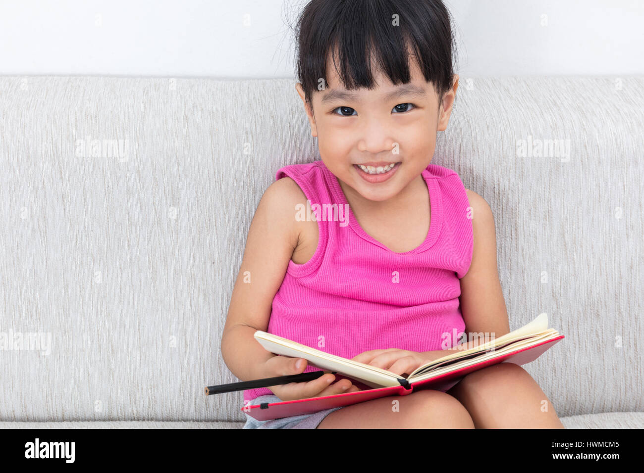 Happy Asian Chinese little girl sitting on sofa writting book in the living room. - Stock Image