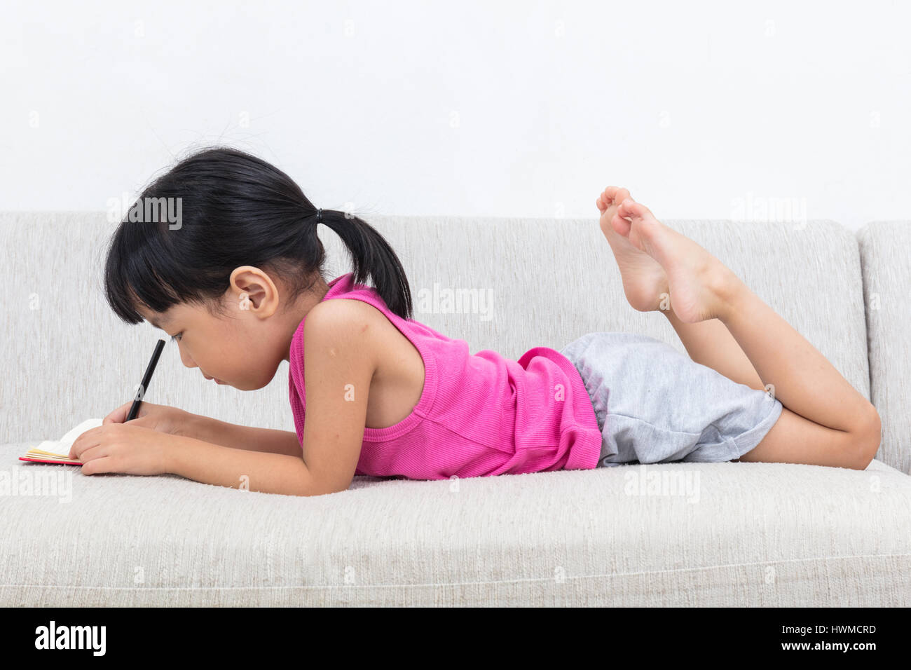 Asian Chinese little girl laying on the sofa writting book in the living room - Stock Image