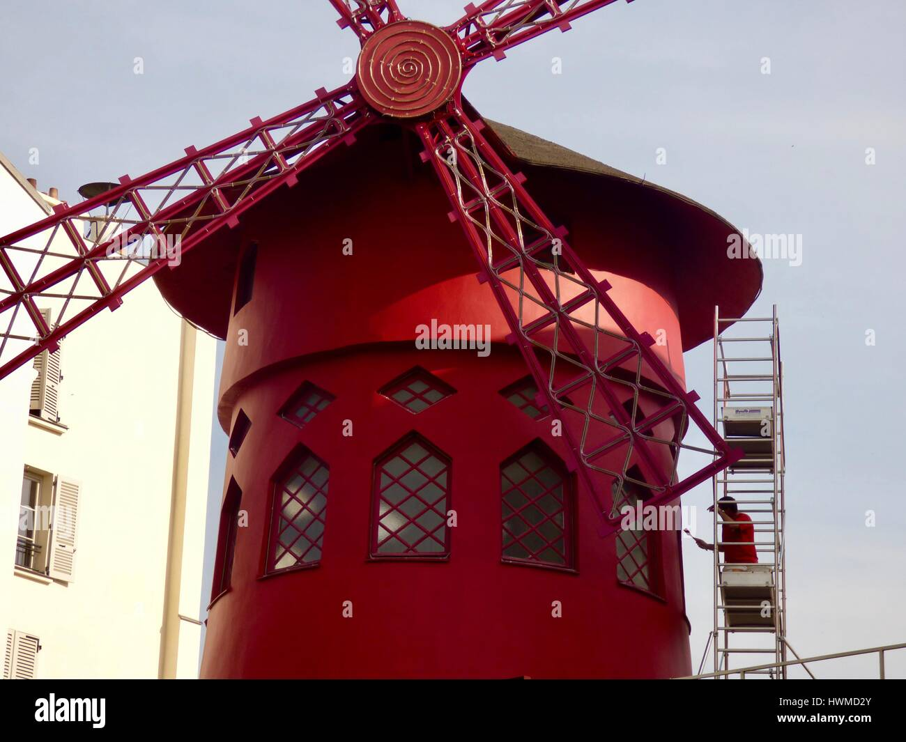 Moulin Rouge. Man wearing red shirt and standing on scaffolding paints the famous red cabaret windmill. Pigalle, - Stock Image