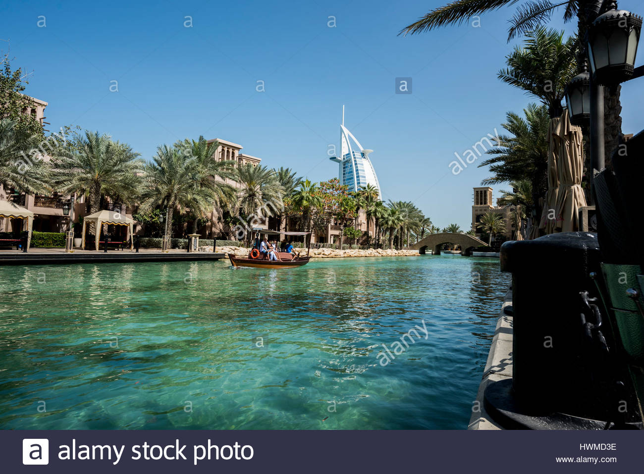 Canal in Souk Madinat Jumeirah with an electrical boat with tourists passing. The iconic Burj Al Arab is standing - Stock Image