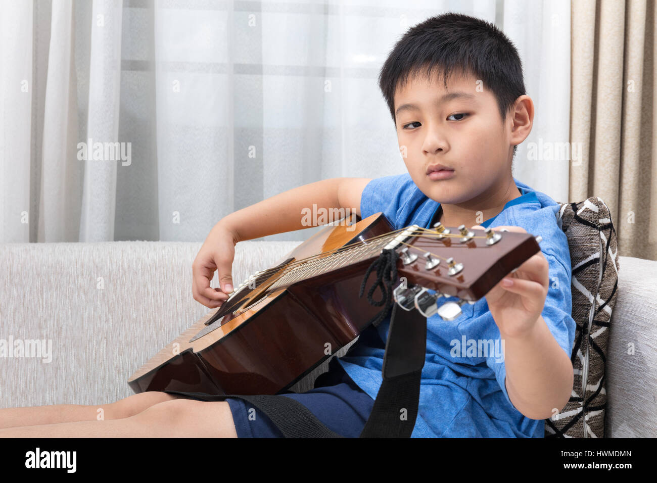 Asian Chinese little boy playing guitar on the sofa in the living room at home. Stock Photo