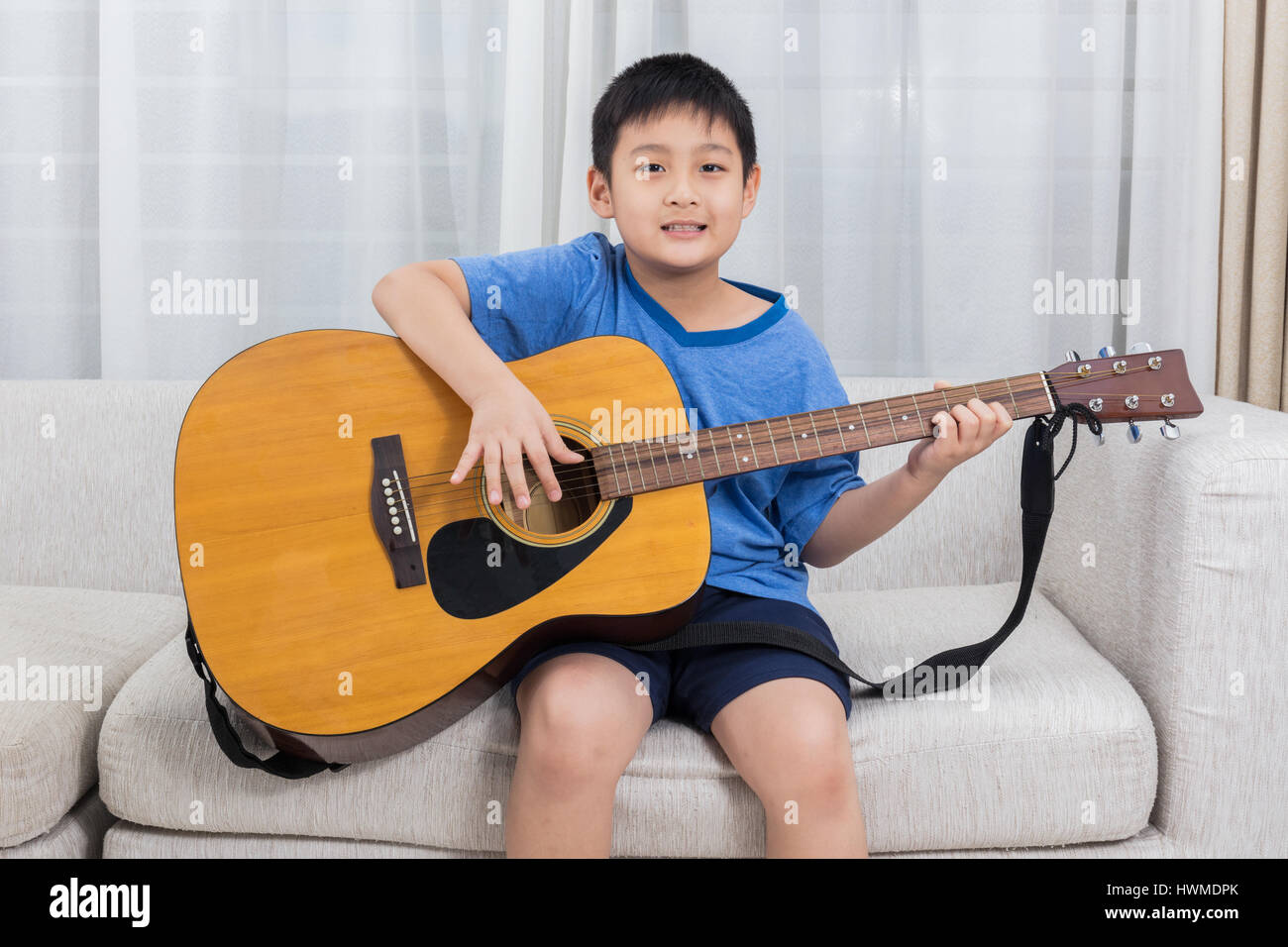 Happy Asian Chinese little boy playing guitar on the sofa in the living room at home. Stock Photo