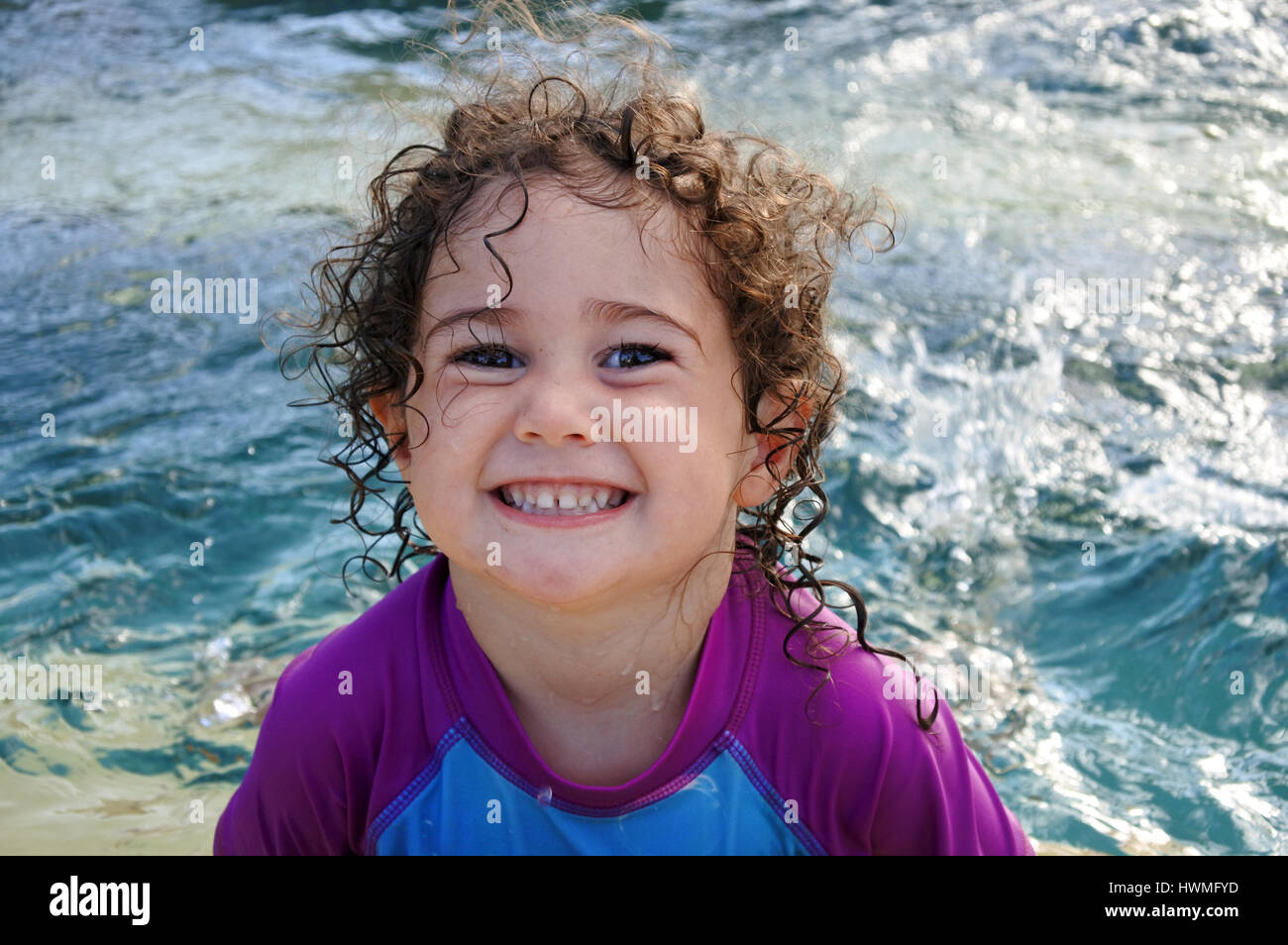 Cheeky little girl (age 2-3) smile in swimming pool during summer holiday. Real people. copy space - Stock Image