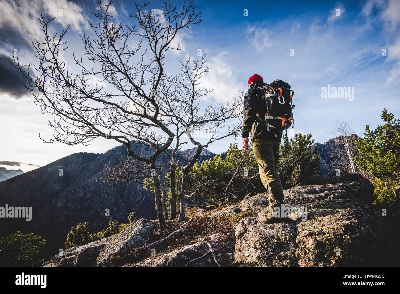 hiker walking on a mountain trail in the woods - wanderlust travel concept with sporty people at excursion in wild Stock Photo