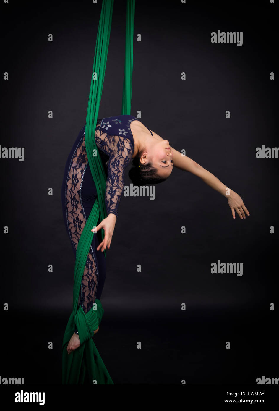Girl's aerial acrobatics in the paintings - dark background. Studio photography of circus performers - Stock Image